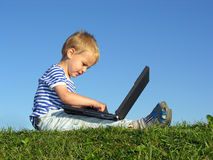Child with notebook sit blue sky. Green grass stock photography