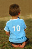 Child number ten. Rear view of the back of a white caucasian boy child wearing a light blue shirt with a number ten on it waiting and sitting on the lawn Royalty Free Stock Photography