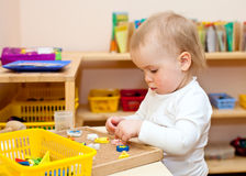 Child at nursery. Little baby girl playing with wooden toys at nursery Stock Photos