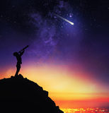 Child observes starry sky with a telescope. Backlit figure of a child from above a mountain expresses a desire during the sight of a falling star stock photos