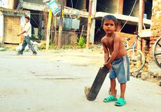 Child obsession for cricket in India. A poor child batting in streets of Lucknow city in India. Cricket is the most favorite game amongst children in India stock photography
