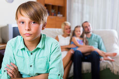Child offended by the parents. Sad teenager son offended by the parents at home Royalty Free Stock Photos