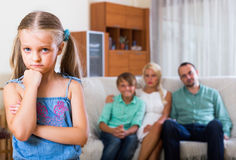 Child offended by the parents. Unhappy little girl offended by the parents at home Stock Photos