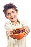 Child offering bowl of cereals Royalty Free Stock Images