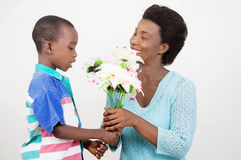 Child offering a flower to his mother for mother's day. This child offered a beautiful flower to his mother for mother's day to prove his love Royalty Free Stock Photo