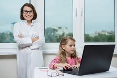 Child in the office is sitting at the table, looking at the laptop. Against the background of woman doctor and window royalty free stock image
