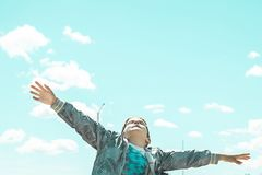 Child with open arms looking up at the sky stock photography
