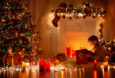 Child Opening Christmas Present, Kid Looking to Light Gift Box. Night Room Xmas Tree and Fireplace Royalty Free Stock Photos