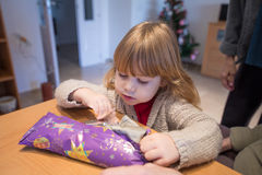 Child opening Christmas present wrapped in paper Stock Photos