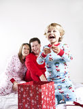 Child opening gifts on Christmas. Excited child opening gifts on Christmas morning. Parents in background Royalty Free Stock Images