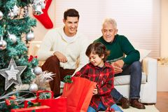 Child opening gifts at christmas at home Royalty Free Stock Images