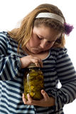 Child Opening Jar. Closeup of a young girl trying to open a jar of pickles, isolated against a white background Royalty Free Stock Image