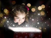 Child opening a magic gift box. With lights and shining around Royalty Free Stock Image