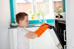 Child opening oven in kitchen. Royalty Free Stock Images