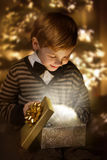 Child opening present box. Magic shining gift. Royalty Free Stock Photos