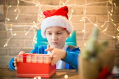 Child opening present from Santa Claus at home. Royalty Free Stock Photography