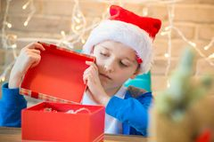 Child opening present from Santa Claus at home. Stock Image