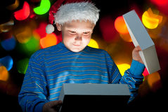 A child opens a box with a gift. On a background of colored lights Royalty Free Stock Images