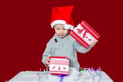 Child opens a gift for Christmas. Child in santa hat opens a gift box for Christmas. holiday mood. Boy surprised by the gift royalty free stock photos
