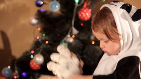Child opens a New Year`s gift near a Christmas tree.  stock footage