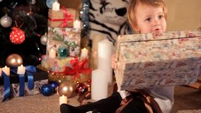 Child opens a New Year`s gift near a Christmas tree.  stock video footage