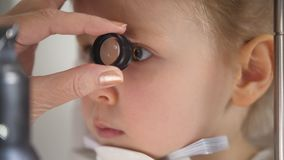 Child in ophthalmology clinic - optometrist diagnosis little blonde girl. Close up stock photos