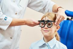 Child optometry concept. Young girl with phoropter during sight testing. Or eye examinations in ophthalmological clinic Royalty Free Stock Images