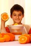 Child and orange. A smiling boy holding a  fresh orange making juice with many oranges around him Stock Photo