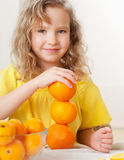 Child with oranges. Happy little girl with fruit at home Stock Photography