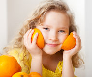 Child with oranges. Happy little girl with fruit at home stock photos