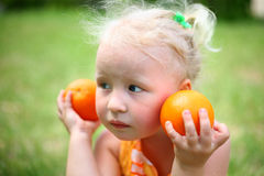 A child with oranges. On the nature Royalty Free Stock Photography
