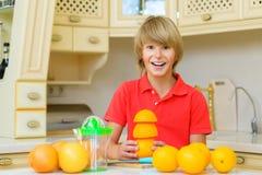 Child with oranges. Boy squeezed fresh orange Royalty Free Stock Photos