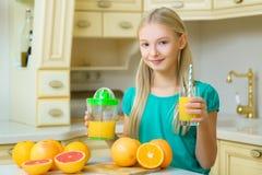 Child with oranges. Girl squeezed fresh orange Stock Photos