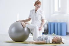Child orthopedist using gym ball Royalty Free Stock Photography
