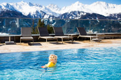 Child in outdoor swimming pool of alpine resort Stock Photography