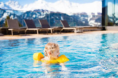 Child in outdoor swimming pool of alpine resort Royalty Free Stock Photo