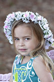Child outdoors with flowers in her hair Stock Photo