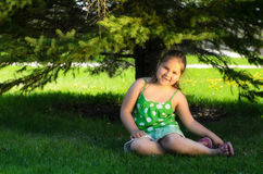 Child Outside. A young girl sitting in the shade of a tree is smiling Stock Images