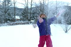 Young girl playing in the snow. Child outside in winter royalty free stock image