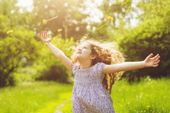 Child outstretched arms enjoying flying yellow dandelion Stock Images