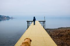Child over a wooden jetty on Lake Maggiore, winter fog on the la. Child over a wooden jetty extending over the water on a winter day with fog Stock Images