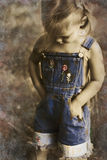 Child in overalls in vintage tones royalty free stock photography