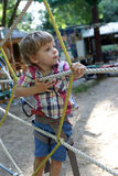 Child overcomes obstacles. In the outdoor playground Stock Photos
