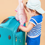 Child packs her things, clothes at luggage Stock Image