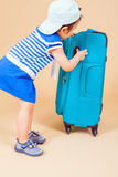 Child packs her things, clothes at luggage Stock Photos