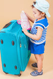 Child packs her things, clothes at luggage Stock Photo