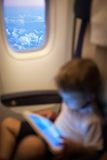 Child with pad in flying plane Royalty Free Stock Image