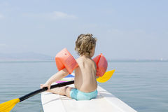 Child and a paddle board. Rear view of a child sitting on a paddle board holding a paddle over a calm sea, MInor Sea, La manga, Murcia, Spain Royalty Free Stock Photography