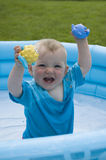 Child paddling in the pool. Child paddling and playing with rubber toys in the inflatable pool Royalty Free Stock Photos