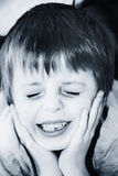 Child in pain. Holds head in hands Royalty Free Stock Images